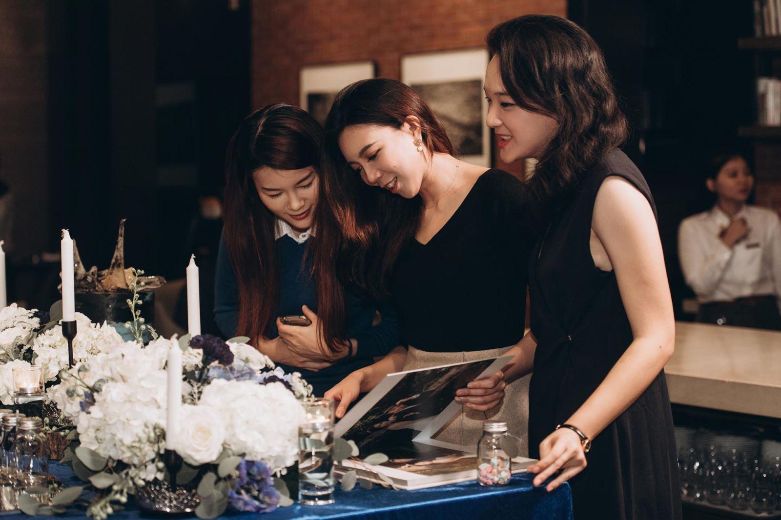 迎賓時刻,一群美女翻閱著新人的婚紗照