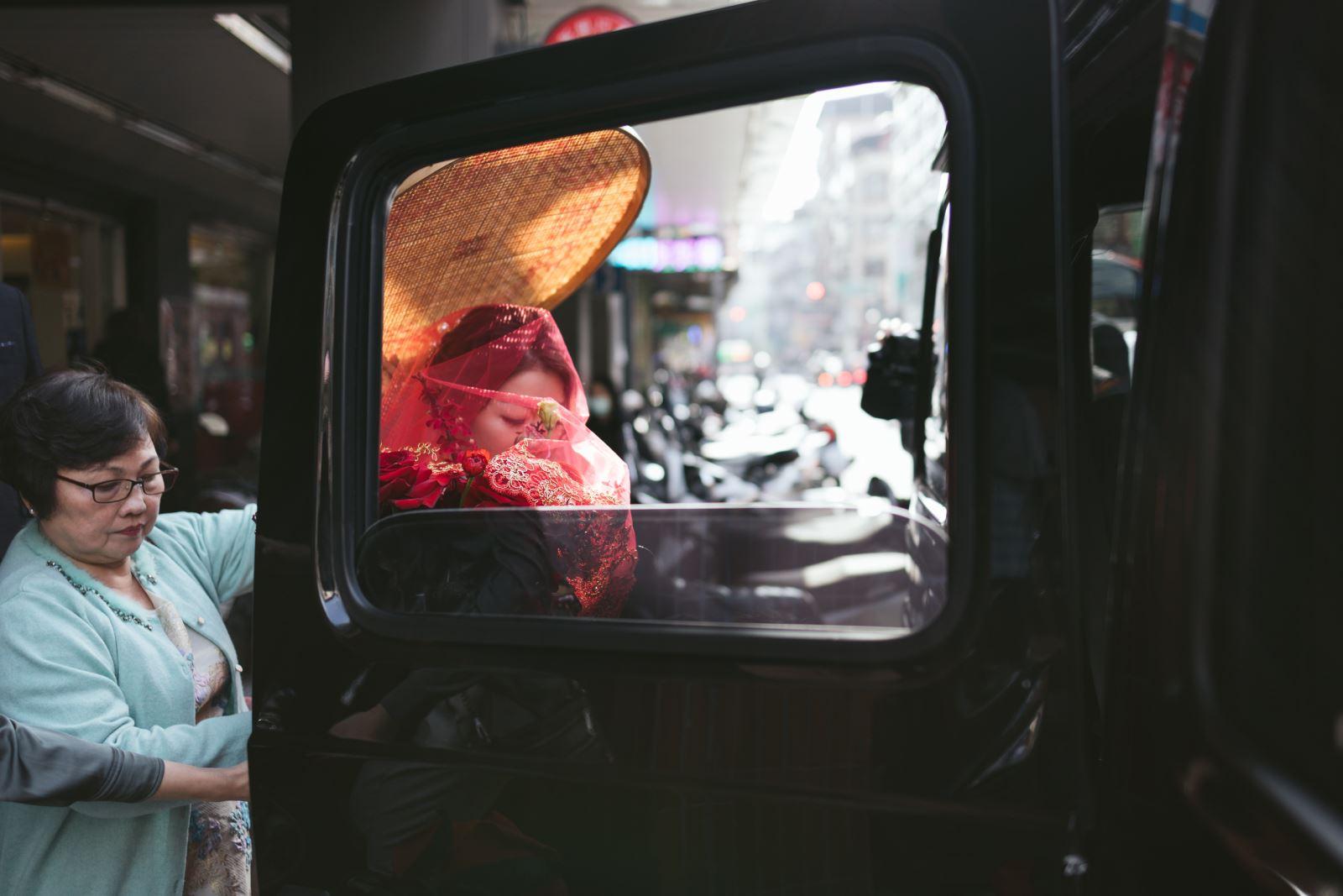 媒人婆手持米篩搭上迎娶車隊,前往新郎家